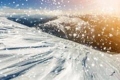 Den härliga vintern landscape Brant bergkullelutning med vit djup snö, avlägsen bergskedjapanorama, stora snöflingor och royaltyfri foto