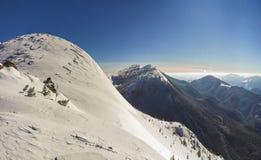Den härliga vintern landscape Brant bergkullelutning med vit djup snö, avlägsen träig bergskedjapanorama som sträcker till royaltyfri fotografi