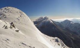 Den härliga vintern landscape Brant bergkullelutning med vit djup snö, avlägsen träig bergskedjapanorama som sträcker till arkivbilder