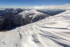 Den härliga vintern landscape Brant bergkullelutning med vit djup snö, avlägsen träig bergskedjapanorama som sträcker till arkivbild