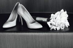Den härliga vita bröllopbuketten av liljor ligger bredvid skorna för brud` s Royaltyfria Foton