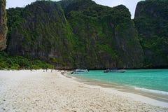 Den härliga vita sandiga stranden bredvid det blåa havet som omges av treed, vaggar thailand Royaltyfri Fotografi