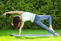 Den härliga vuxna kvinnan som gör yoga på sommar, parkerar Arkivbilder