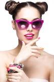Den härligt flickan i rosa solglasögon med ljus makeup och färgrikt spikar Härlig le flicka royaltyfri bild