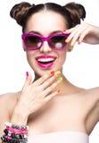 Den härligt flickan i rosa solglasögon med ljus makeup och färgrikt spikar Härlig le flicka royaltyfria foton