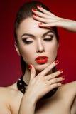 Den härligt kvinnan med aftonsmink och rött spikar Royaltyfri Foto
