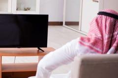 Den hållande ögonen på tv:n för arabisk man hemma arkivfoto