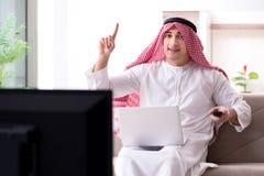 Den hållande ögonen på tv:n för arabisk man hemma royaltyfria bilder