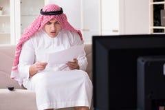 Den hållande ögonen på tv:n för arabisk man hemma royaltyfri fotografi