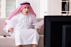 Den hållande ögonen på tv:n för arabisk man hemma arkivbild