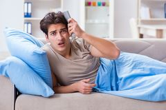 Den hållande ögonen på tv:n för man från hållande fjärrkontrollenhet för säng royaltyfria foton