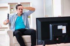 Den hållande ögonen på tv:n för man hemma arkivfoton