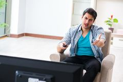 Den hållande ögonen på tv:n för man hemma royaltyfria foton