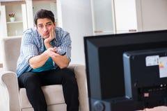 Den hållande ögonen på tv:n för man hemma arkivbild