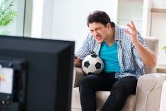 Den hållande ögonen på tv:n för man hemma royaltyfri fotografi