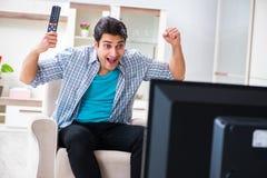 Den hållande ögonen på tv:n för man hemma royaltyfria bilder