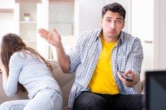 Den hållande ögonen på tv:n för par hemma royaltyfri foto