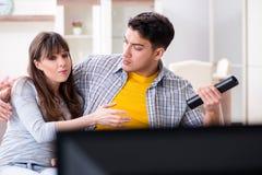 Den hållande ögonen på tv:n för par hemma arkivfoto