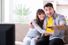 Den hållande ögonen på tv:n för par hemma arkivbilder