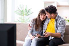 Den hållande ögonen på tv:n för par hemma royaltyfri bild
