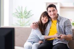 Den hållande ögonen på tv:n för par hemma arkivbild