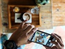 Den hållande smartphonen tar ett foto av koppen för Lattekonstkaffe på trämagasinet arkivbilder