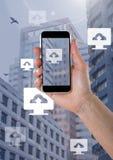 Den hållande telefonen och datormolnet laddar upp symboler i stad Fotografering för Bildbyråer