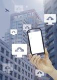 Den hållande telefonen och datormolnet laddar upp symboler i stad Arkivfoton