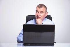 Den höga affärsmannen är eftertänksam på bärbara datorn Arkivbild