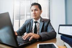 Den höga affärsmannen i grå färger passar sammanträde och användabärbara datorn på hans arkivfoton