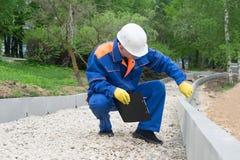 Den höga arbetaren kontrollerar riktigheten av konstruktionen av vägen genom att använda ett mäta band arkivfoto