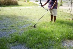 Den höga arbetaren mejar gräs i gården med den elektriska handbeskäraren royaltyfri bild
