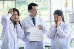 Den höga asiatiska forskaren har att tilldela nytt jobb till studenter i laboratorium royaltyfri foto