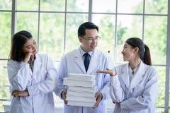 Den höga asiatiska forskaren har att tilldela nytt jobb till studenter i laboratorium med lycka arkivfoton