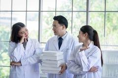 Den höga asiatiska forskaren har att tilldela nytt jobb till studenter i laboratorium med lycka fotografering för bildbyråer