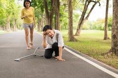 Den höga asiatiska kvinnan med svagt sammanträde på golv, når han har fallit ner, kvinnligt, tar omsorg och service royaltyfria bilder