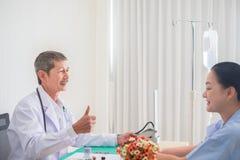 Den h?ga asiatiska l?karen lyftte fingret och blick p? den kvinnliga patienten med leende fotografering för bildbyråer