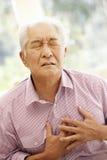 Den höga asiatiska mannen med bröstkorgen smärtar Arkivfoto