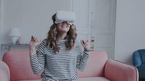 Den höga emotionella nätta flickan håller ögonen på 360 grad video hemma och att bära VR-hörlurar med mikrofon Hon är myc stock video
