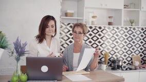 Den höga farmodern och den unga sondottern sitter på tabellen och kontrollerar information med att knyta kontakt bärbara datorn arkivfilmer