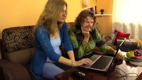 Den höga farmorkvinnan och den gravida sondottern använder bärbara datorn lager videofilmer