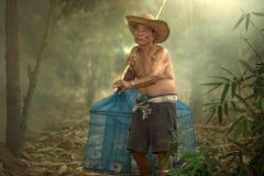 Den höga gamala mannen är fiskaren i thailändska Mekong River och Laos gå Royaltyfria Foton