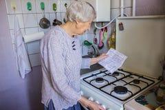 Den höga gamla hemmafrun hemma och undersöker gas- och elektricitetsräkningar royaltyfria foton