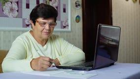 Den höga gamla kvinnan i glasögon som kontrollerar kostnader av dagstidningen, uppta som omkostnad på bärbara datorn hemma stock video