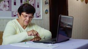 Den höga gamla kvinnan i glasögon som kontrollerar kostnader av dagstidningen, uppta som omkostnad på bärbara datorn hemma lager videofilmer
