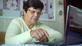 Den höga gamla kvinnan i glasögon som kontrollerar kostnader av dagstidningen, uppta som omkostnad på bärbara datorn hemma arkivfilmer