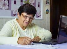 Den höga gamla kvinnan i glasögon som kontrollerar kostnader av dagstidningen, uppta som omkostnad på bärbara datorn hemma arkivbilder