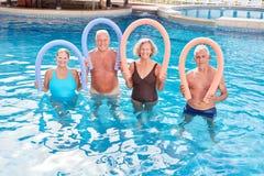Den höga gruppen gör en Aquafitness kurs med att simma nudeln arkivbilder