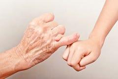 Den höga handen och barnet för gammal kvinna räcker att haka deras fingrar royaltyfri bild