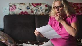 Den höga hushållkvinnan öppnar ett brev och är bestämt chockad och förvånad i en negativ väg vid den höga begäran av pengar w